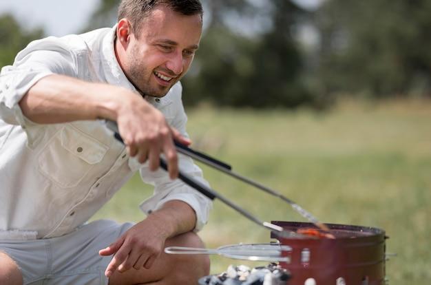 Homem sorridente a frequentar o churrasco ao ar livre