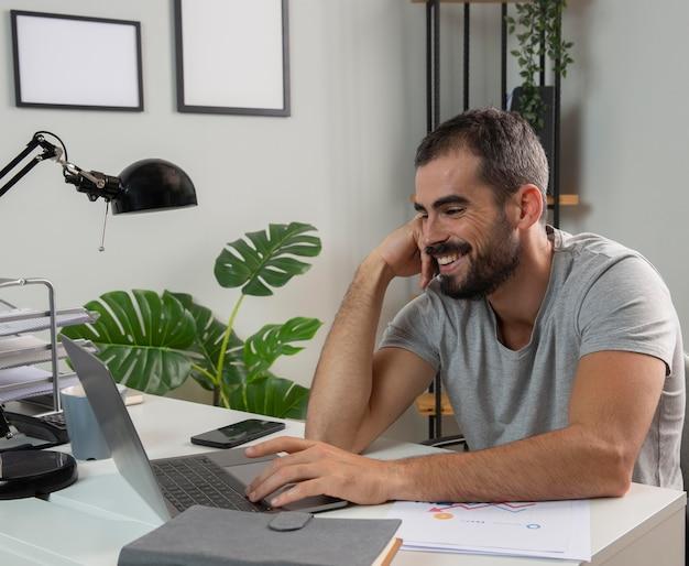 Homem sorridente a gostar de trabalhar em casa