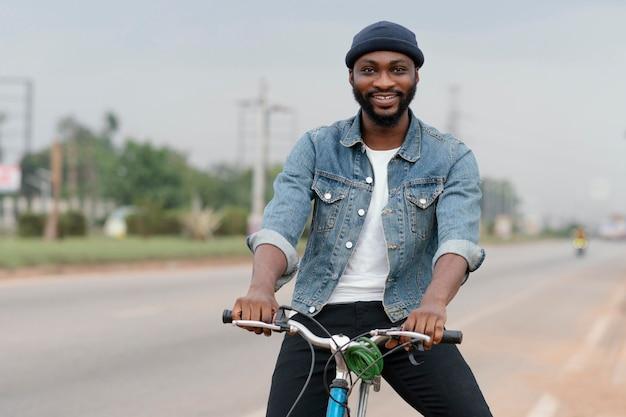 Homem sorridente a posar de bicicleta