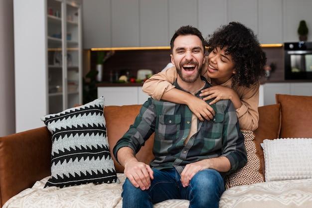 Homem sorridente abraçado por sua namorada