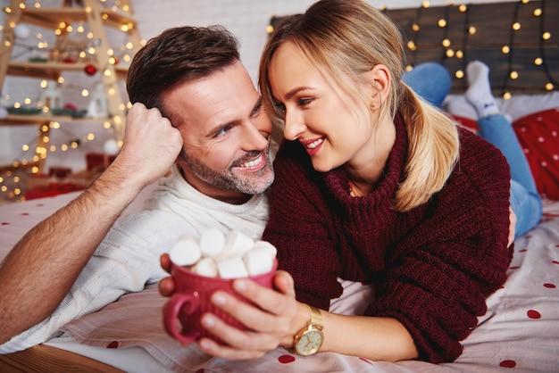 Homem sorridente abraçando a namorada no natal