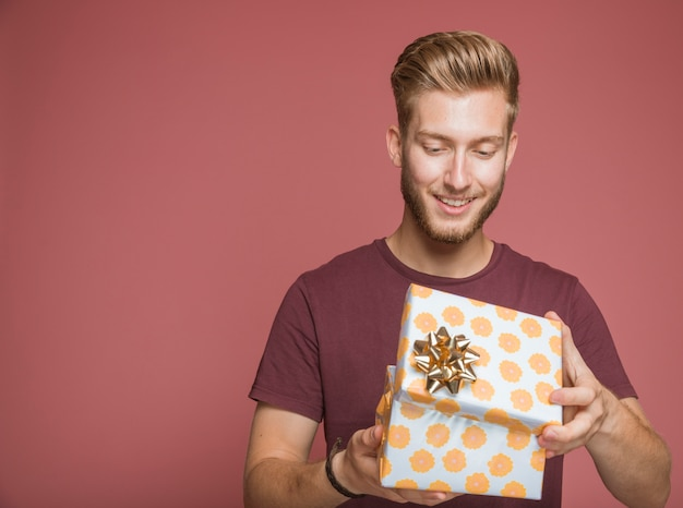 Homem sorridente, abrindo a caixa de presente floral com laço dourado