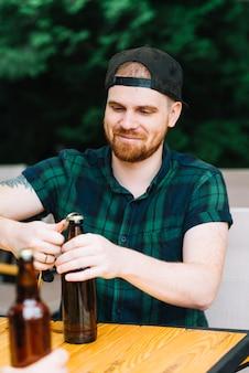 Homem sorridente, abrindo a tampa de garrafa com abridor na mesa de madeira