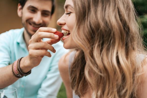 Homem sorridente, alimentando sua jovem esposa feliz com morango. casal alegre com lindos sorrisos
