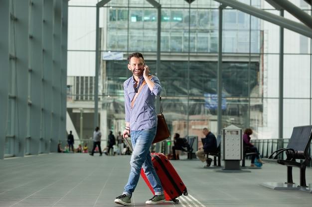 Homem sorridente andando na estação de trem com um telefone