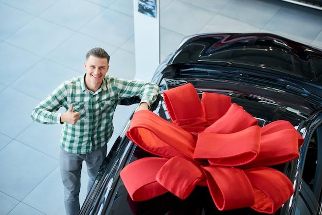 Homem sorridente, aparecendo o polegar perto do carro.