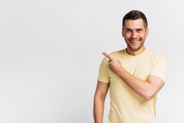 Homem sorridente apontando com espaço de cópia