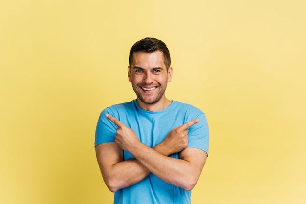 Homem sorridente apontando em direções diferentes