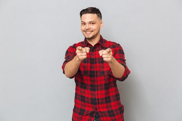Homem sorridente apontando para a câmera