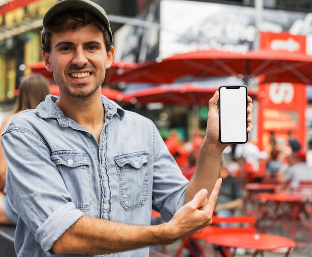 Homem sorridente apontando para smartphone