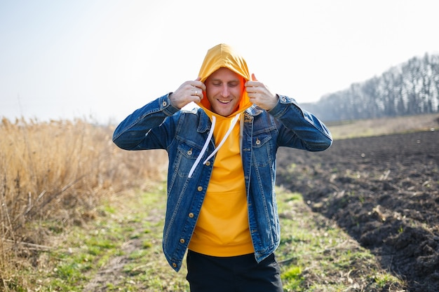 Homem sorridente, apreciando o vento soprando na floresta. homem feliz, sentindo alegria enquanto caminhava na natureza, espaço livre em fundo de árvores verdes. amor pela vida, alegria, ar puro, conceito de renovação