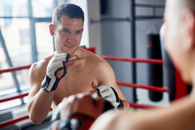 Homem sorridente, aproveitando a luta de boxe no ringue