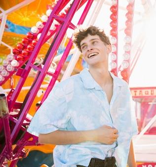Homem sorridente, aproveitando o tempo no parque de diversões