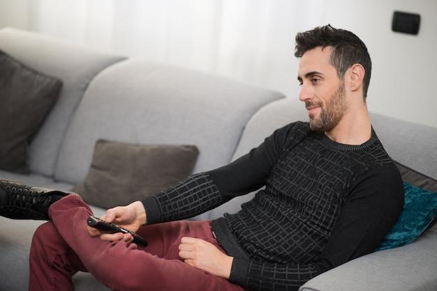 Homem sorridente, assistindo televisão