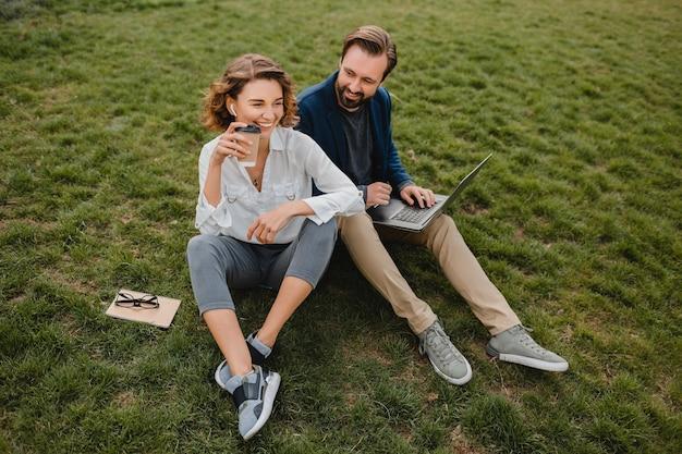 Homem sorridente atraente e mulher conversando sentado na grama em um parque urbano, fazendo anotações
