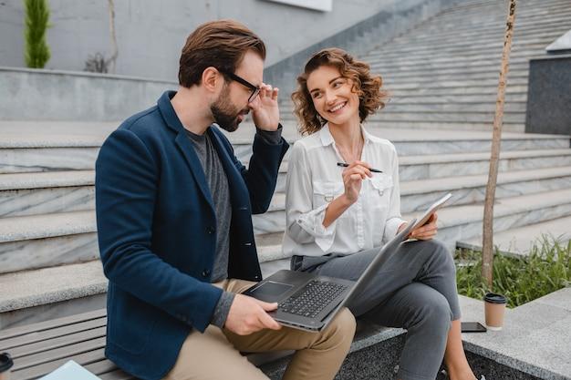 Homem sorridente atraente e mulher conversando, sentados em um banco no centro urbano da cidade, fazendo anotações