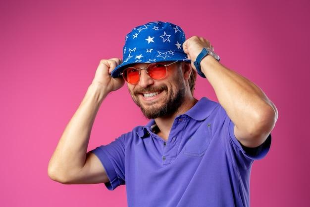 Homem sorridente barbudo engraçado usando chapéu de praia e óculos escuros contra rosa