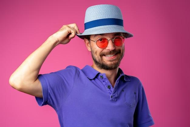 Homem sorridente barbudo engraçado usando chapéu de praia e óculos escuros