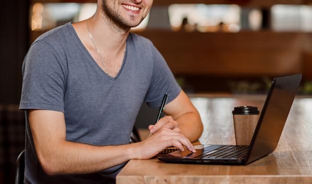 Homem sorridente, bebendo café e trabalhando no café.