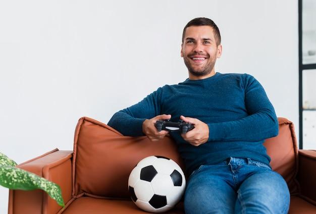 Homem sorridente brincando com joystick