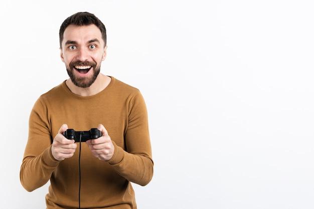 Homem sorridente, brincando com o controlador de jogo