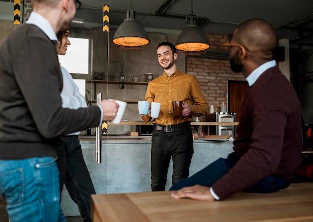 Homem sorridente carregando canecas com café para os colegas