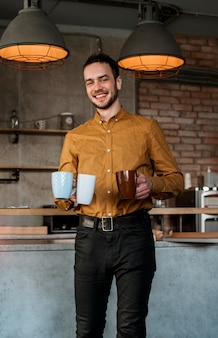 Homem sorridente carregando canecas com café