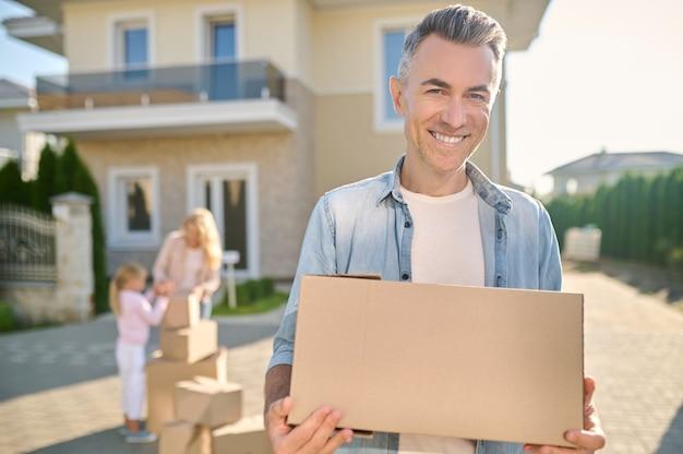 Homem sorridente carregando coisas em uma caixa na rua