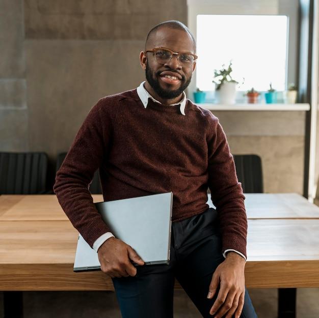 Homem sorridente carregando laptop