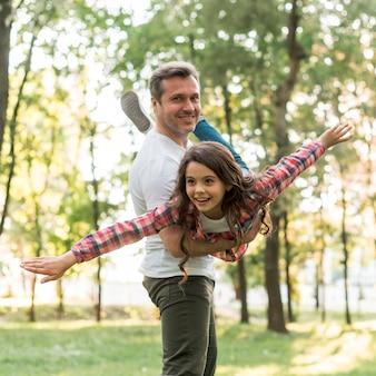 Homem sorridente carregando sua filha no parque