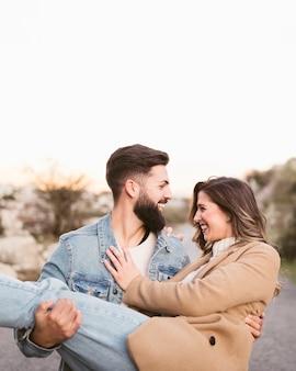 Homem sorridente carregando sua namorada