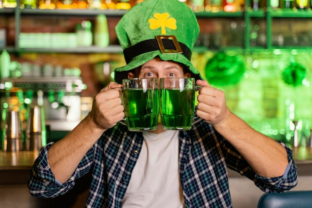 Homem sorridente celebrando st. dia de patrick no bar com cerveja