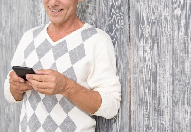 Homem sorridente close-up com smartphone e fundo de madeira