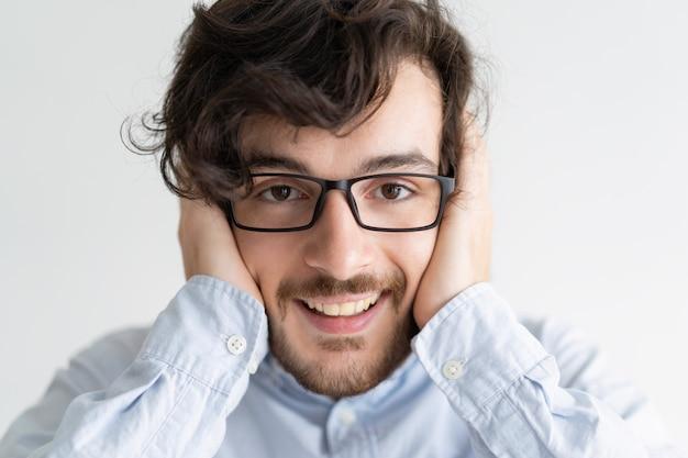 Homem sorridente, cobrindo as orelhas com as mãos e olhando para a câmera