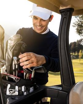 Homem sorridente colocando tacos no carrinho de golfe