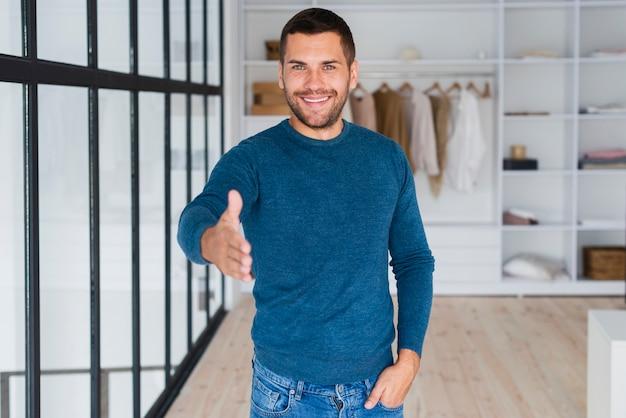 Homem sorridente com a mão em direção à câmera para apertar as mãos
