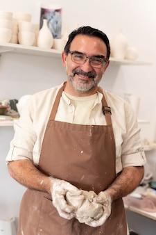 Homem sorridente com avental segurando argila