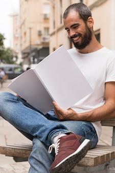 Homem sorridente com barba lendo livro ao ar livre