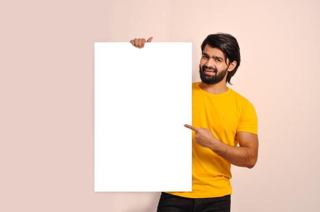 Homem sorridente com barba segurando banner publicitário apontando com o dedo