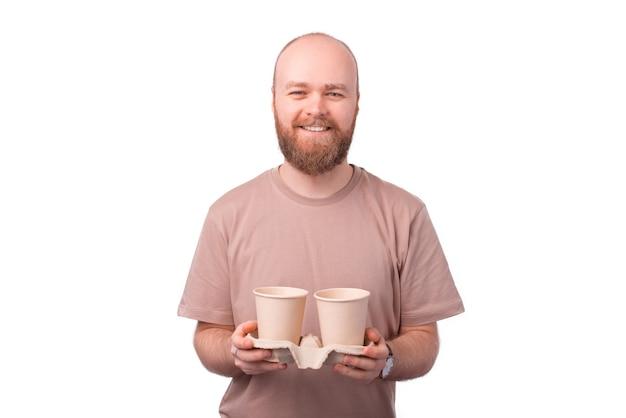 Homem sorridente com barba segurando duas xícaras de café para viagem