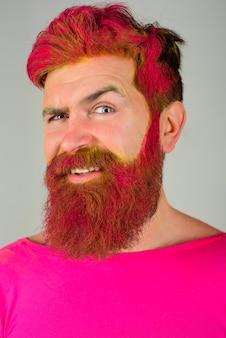 Homem sorridente com barba tingida e cabelo moderno com publicidade de cabeleireiro penteado de cabelo rosa e