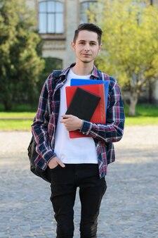 Homem sorridente com bolsa segurando notebooks campus