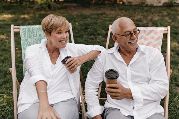 Homem sorridente com cabelo grisalho e bigode em óculos e camisa de manga longa branca, segurando a xícara de café e posando com senhora alegre no parque.