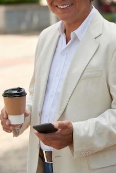 Homem sorridente com café para viagem