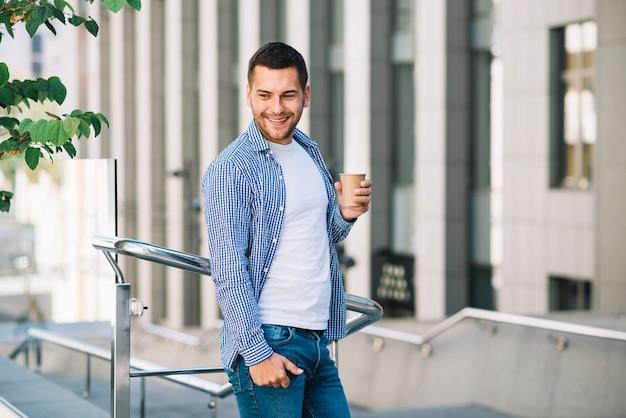 Homem sorridente com café perto do corrimão