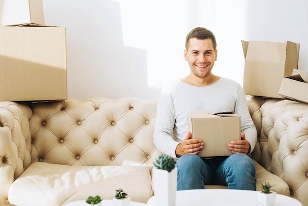 Homem sorridente com caixa de papelão