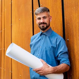 Homem sorridente com camisa azul e esquemas