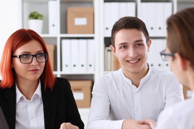 Homem sorridente com camisa cumprimentando-se com um aperto de mão no escritório