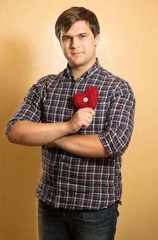 Homem sorridente com camisa quadriculada segurando um coração vermelho decorativo