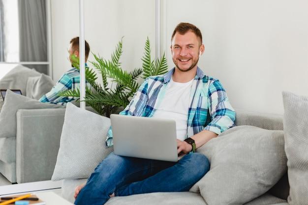 Homem sorridente com camisa sentado relaxado no sofá em casa à mesa trabalhando online no laptop de casa